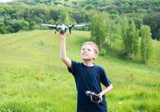准备微笑的年轻的男孩发射RC飞行 背景美好的做的本质向量 图库摄影