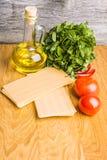 准备意大利烤宽面条用新鲜的红色蕃茄和薄菏在干面团板料  免版税库存图片