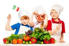 准备意大利膳食的三位年轻厨师 免版税库存照片
