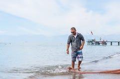 准备捕鱼网的两位渔夫开始营业日在海洋,海海岸  健康生活方式 正面人的情感,感受 图库摄影