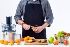 准备新鲜水果汁的匿名人使用电榨汁器,在白色背景的健康生活方式戒毒所概念 库存照片