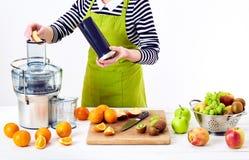 准备新鲜水果汁的匿名妇女使用电榨汁器,在白色背景的健康生活方式戒毒所概念 库存图片
