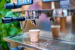 准备新鲜的咖啡和涌入纸杯的咖啡机器 免版税库存图片