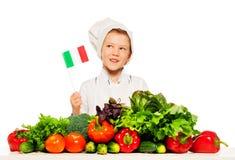 准备新鲜的沙拉的厨师的无边女帽的意大利男孩 免版税库存图片