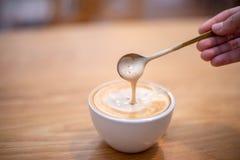 准备新鲜的热奶咖啡的男性手的特写镜头图象 图库摄影