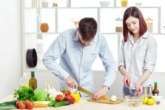 准备新鲜蔬菜的健康沙拉爱恋的愉快的夫妇在厨房里 库存图片