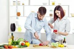 准备新鲜蔬菜的健康沙拉爱的微笑的夫妇在厨房里 库存照片