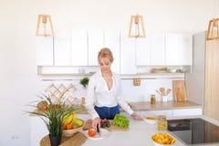 准备新鲜蔬菜的沙拉在切板的俏丽的女孩 库存照片