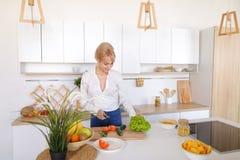 准备新鲜蔬菜的沙拉在切板的俏丽的女孩 免版税图库摄影