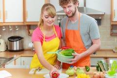 准备新鲜蔬菜食物沙拉的夫妇 免版税库存图片