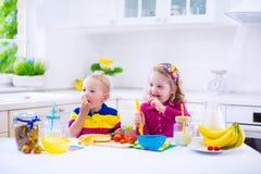 准备早餐的孩子在一个白色厨房里 免版税库存图片