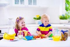 准备早餐的孩子在一个白色厨房里 免版税库存照片