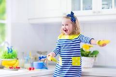 准备早餐的小女孩在一个白色厨房里 免版税库存照片