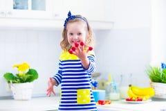 准备早餐的小女孩在一个白色厨房里 库存照片