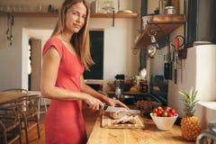 准备早餐的美丽的妇女在她的厨房里 免版税图库摄影