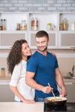 准备晚饭和看其中每一的愉快的夫妇 免版税库存照片