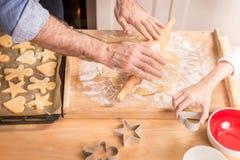 准备曲奇饼的父亲的和女儿的手烘烤 库存图片