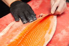 准备有刀子的特写镜头新鲜的三文鱼鱼内圆角在红色切板在餐馆专业厨房里  概念日语 库存照片
