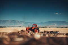 准备有温床耕地机的拖拉机的农夫土地 免版税库存照片