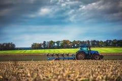 准备有温床耕地机的拖拉机的农夫土地 免版税库存图片
