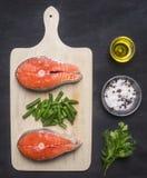 准备未加工的鲑鱼排用草本,盐、胡椒和其他调味料,两块牛排在切板说谎,在一黑backgrou 库存图片