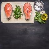 准备未加工的鲑鱼排用草本,盐、胡椒和其他调味料,两块牛排在切板说谎,在黑backgr 免版税图库摄影