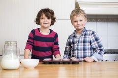 准备杯形蛋糕的微笑的孩子在厨房里 免版税库存图片