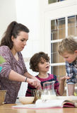 准备杯形蛋糕面团的家庭在厨房里 免版税库存图片