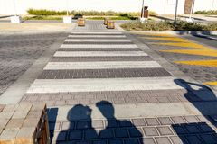 准备步行者的剪影在行人穿越道附近穿过路 免版税库存图片