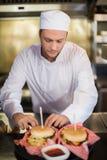准备汉堡的严肃的男性厨师在商业厨房里 免版税库存照片
