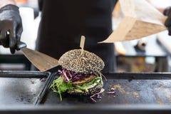 准备汉堡的厨师在国际都市街道食物节日的格栅板材 免版税图库摄影
