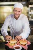 准备汉堡的男性厨师在商业厨房里 免版税库存图片