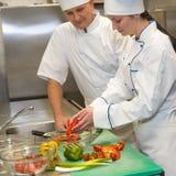 准备沙拉的厨师在餐馆的厨房里 免版税库存照片