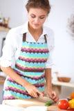 准备沙拉的微笑的妇女在厨房里 免版税库存照片