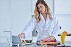 准备沙拉的微笑的美丽的妇女在早晨少妇早餐照片浴巾的 饮食 健康生活方式 库存照片