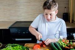 准备沙拉的男孩在厨房里 免版税库存照片