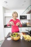 准备沙拉的资深妇女在厨台 免版税库存图片