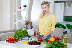 准备沙拉的年轻主妇在厨房里 免版税库存图片