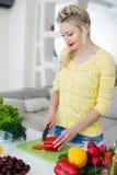 准备沙拉的年轻主妇在厨房里 图库摄影