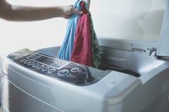 准备洗涤周期 洗衣机,有衣裳的手 库存图片