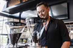 准备浓咖啡的愉快的年轻人,当工作作为在a时的barista 免版税图库摄影