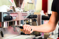 准备浓咖啡的Barista在咖啡壶 免版税图库摄影