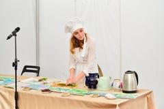 准备清凉茶的女孩厨师在介绍在festiv 库存照片