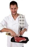 准备牛排的可爱的白种人厨师男 免版税库存图片