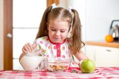 准备玉米片用牛奶的孩子 免版税图库摄影