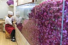 准备玫瑰蛋糕的年轻纳西妇女 罗斯蛋糕是丽江的专长 免版税库存图片