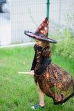 准备的万圣夜 邪恶的巫婆的衣服的女孩假装她在笤帚飞行 图库摄影