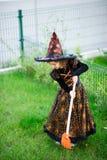 准备的万圣夜 邪恶的巫婆的衣服的女孩清洗草坪犁耙 图库摄影