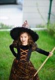 准备的万圣夜 邪恶的巫婆的衣服的女孩清洗草坪犁耙 库存图片