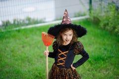 准备的万圣夜 邪恶的巫婆的衣服的女孩清洗草坪犁耙 免版税图库摄影